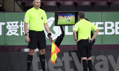 Referee Kevin Friend checks for a foul and consults VAR in a match between Manchester United and Burnley. (imago Images)